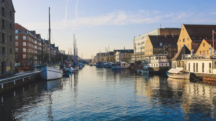 Wide shot of boats on the body of water near buildings in christianshavn, copenhagen, denmark - Scandinavian languages